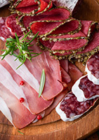 Assorted cold cuts with rosemary on chopping board