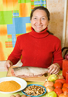 woman is cooking red fish